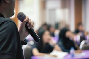close-up-man-lecturer-speak-with-microphone-in-selective-focus_40822-54-300x200