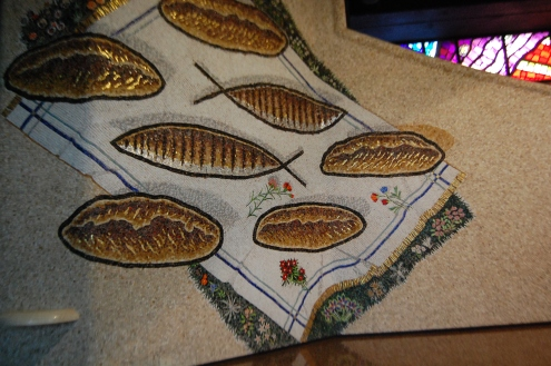 Sul mosaico a tutta parete, a sinistra, il grande mantile bianco sul prato con 5 pani e 2 pesci.